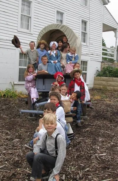 School kids posed by the covered wagon while on a school tour