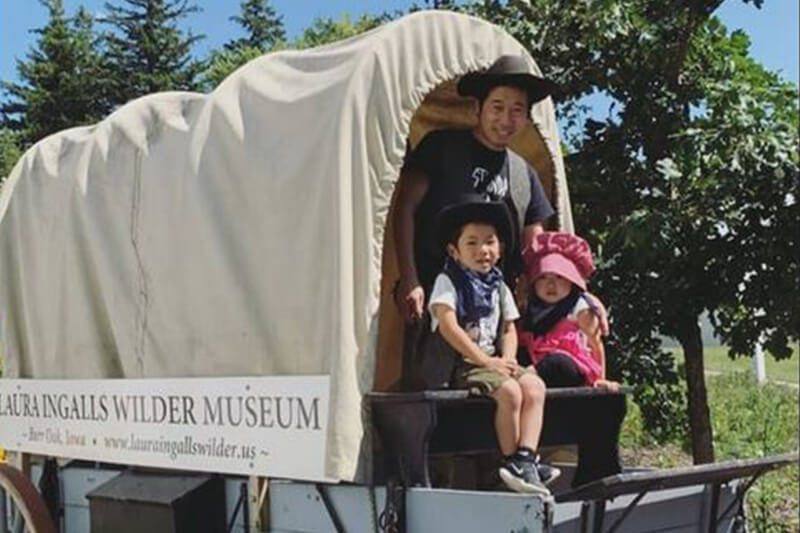 Family dressed in pioneer costumes in the covered wagon